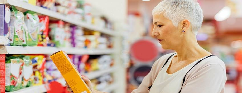 Woman shopping in a grocery store looking at products packaged using Advantra packaging adhesive.