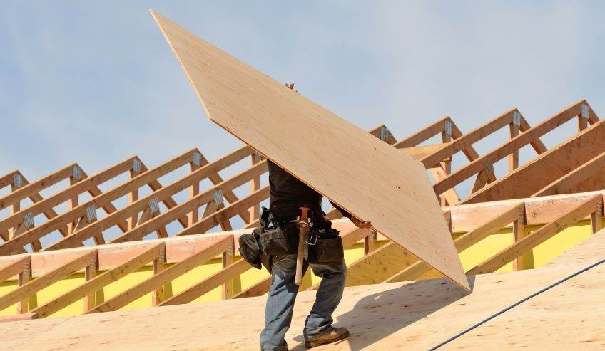 Man walking on roof with a piece of plywood